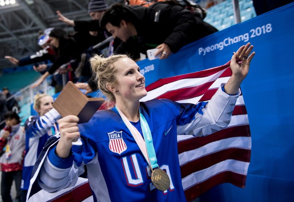 Jocelyne Lamoureux-Davidson walks with her gold medal and an American flag after the U.S. women's ice hockey team's overtime victory against Canada during the Pyeongchang 2018 Winter Olympic Games on February 22, 2018.
