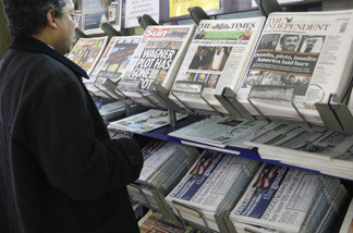 A man views a news stand displaying national newspapers, some carrying the story on WikiLeaks' release of classified U.S. State Department documents, at a newsagent in central London, Monday, Nov. 29, 2010.