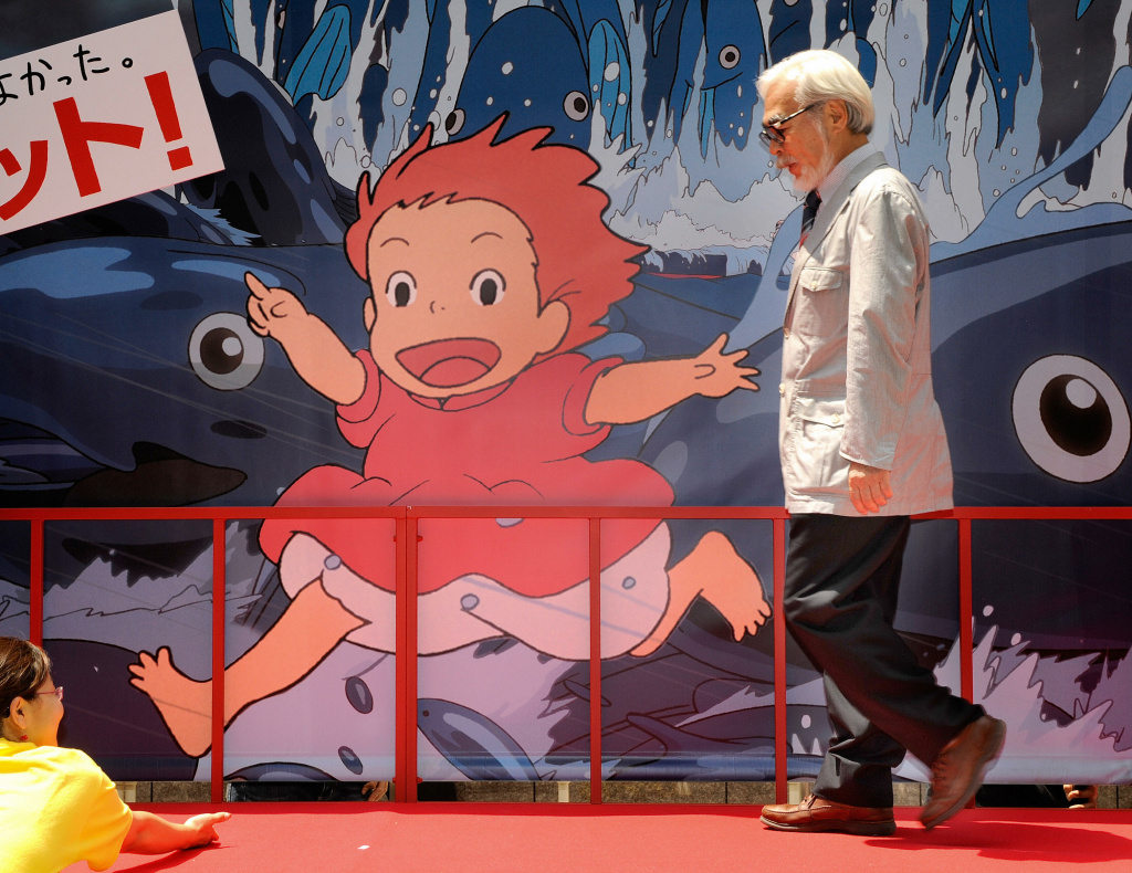 "Oscar-winning Japanese animator and film director Hayao Miyazaki walks past a advertising board for a photo session following the release of his new animated movie ""Ponyo on the Cliff by the Sea"" at a theater in Tokyo on July 19, 2008."