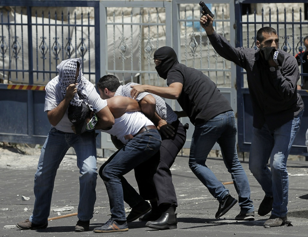 Israeli undercover policemen, one holding a gun, arrest a Palestinian (2ndL) during clashes following traditional Friday prayers near the Old City in East Jerusalem on July 25, 2014.