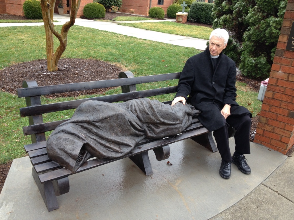 Rev. David Buck sits next to the <em>Jesus the Homeless</em> statue that was installed in front of his church, St. Alban's Episcopal, in Davidscon, N.C.