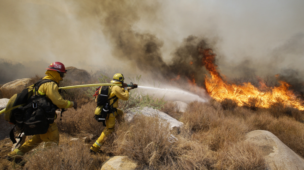 Firefighters battle a wildfire, earlier this month in Cabazon, Calif.