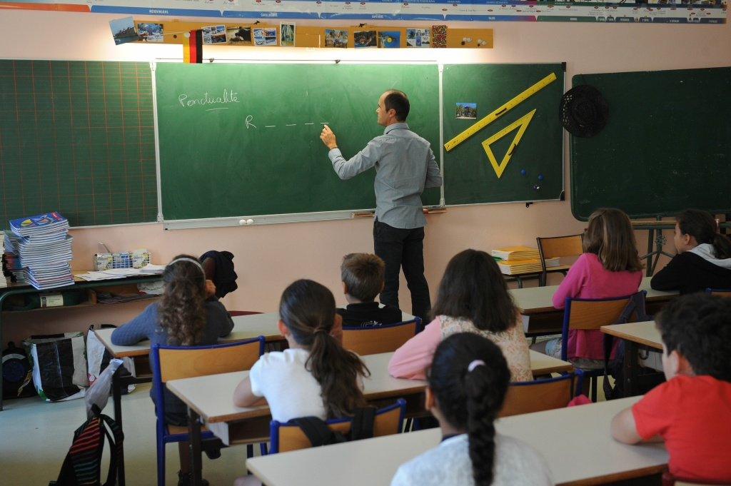 A teacher writes on a blackboard in front of pupils during a class at the Pierre Levee primary school in La Jarne, France.