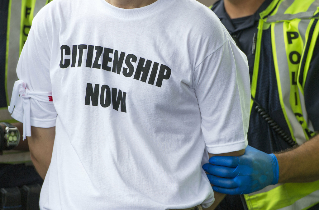 A demonstrator is arrested by US Capitol Police during an immigration protest near the US Capitol in Washington, DC, August 1, 2013. Some 40 pro-immigration activists have been arrested outside the US Capitol after blocking traffic while pushing for passage of legislation overhauling the system.