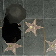 LOS ANGELES, CA - JUNE 28: A tourist holding an umbrella to shield herself from the sun walks on Hollywood Walk of Fame stars during a major heat wave in Southern California on June 28, 2013 in downtown Los Angeles, California. Temperatures are expected to be in the triple digits in most areas of Southern California. According to the national Weather Service, the heat wave is expected to linger into early next week prompting heat advisories and opening of cooling centers.  (Photo by Kevork Djansezian/Getty Images)