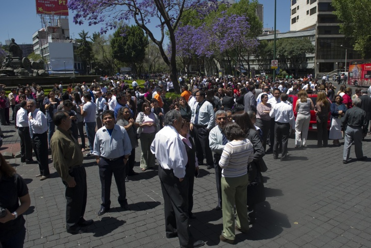 People run to safety on the streets of Mexico City after a strong quake hits Mexico on March 20, 2012.