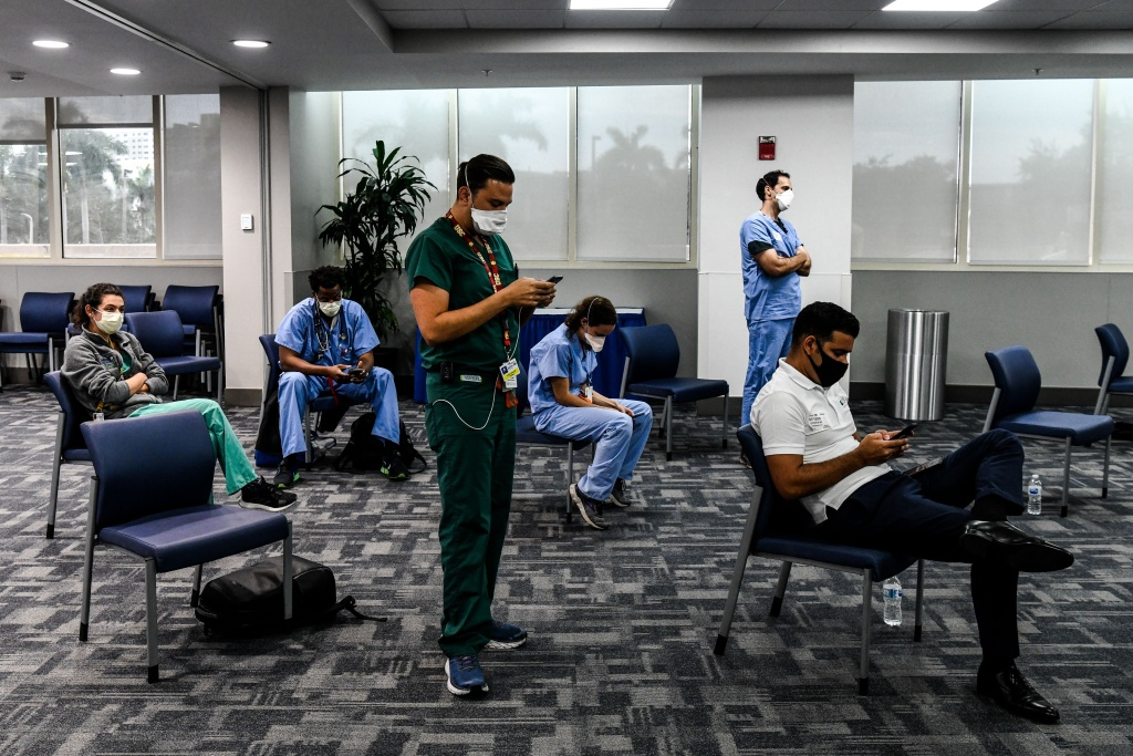 Students and doctors of Medical Science listen to the governor of Florida during a press conference to address the rise of coronavirus cases in the state, at Jackson Memorial Hospital in Miami, on July 13, 2020.