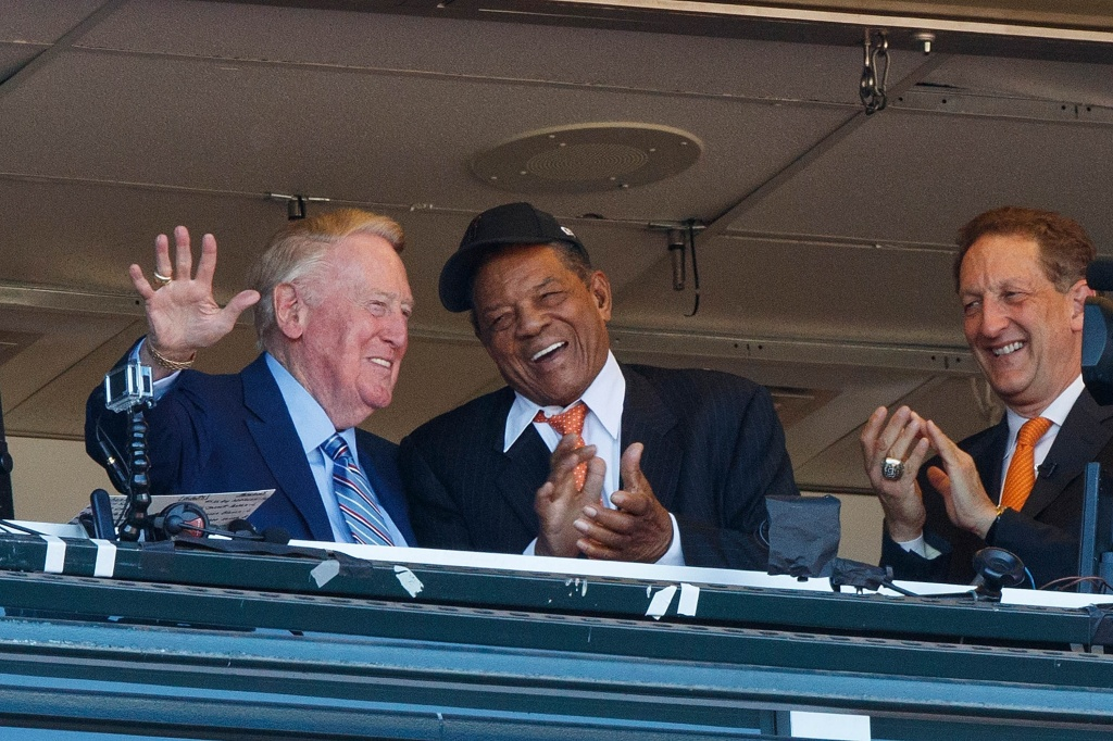 Los Angeles Dodgers broadcaster Vin Scully is congratulated on the last game of his 67-year career by hall of famer Willie Mays and San Francisco Giants CEO Larry Baer during the fourth inning at AT&T Park on October 2, 2016 in San Francisco, California. The San Francisco Giants defeated the Los Angeles Dodgers 7-1.