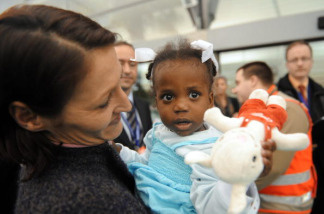 A mother holds her adopted child arriving from Haiti