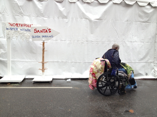 A man on a wheelchair rides past the Christmas tent at LA Mission, after finishing his Christmas eve meal.