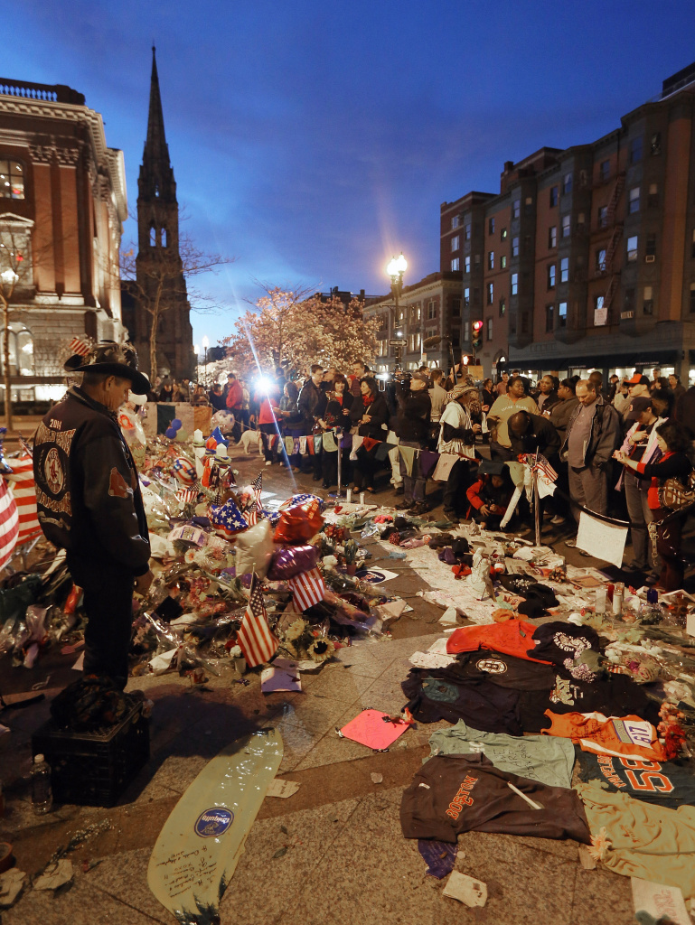 People gather at a makeshift memorial for victims of the Boston Marathon bombings. The surviving suspect in the case, Dzhokhar Tsarnaev, remains in the hospital. His older brother, also a a suspect, was killed by police. The brothers are from an immigrant family with roots in the former Soviet Union, and this has stoked debate as the Senate contemplates an immigration reform bill.
