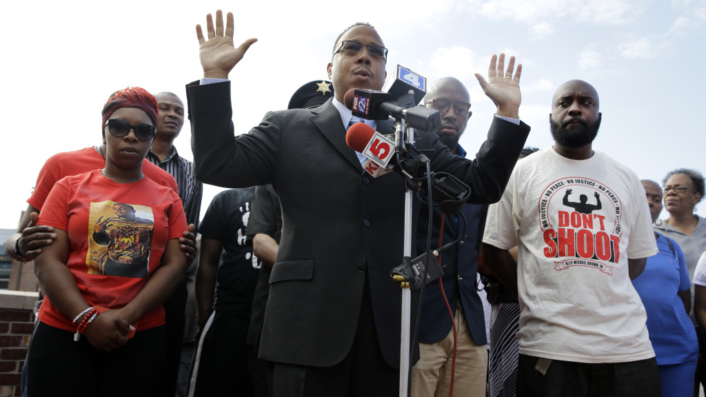 Michael Brown's parents Lesley McSpadden (left) and Michael Brown Sr. (right) flank attorney Anthony Gray as he speaks at a news conference held Tuesday, one month after Michael Brown was shot and killed in Ferguson, Mo.