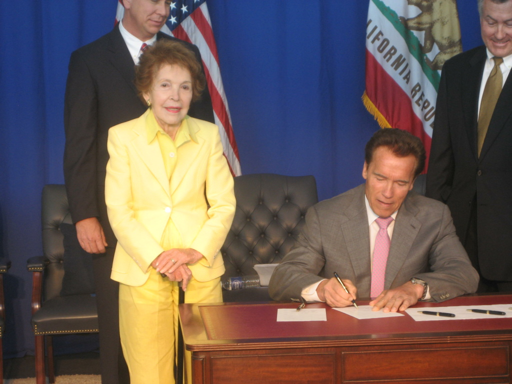 California Governor Arnold Schwarzenegger signs bills as former First Lady Nancy Reagan looks on at the Ronald Reagan Library in Simi Valley