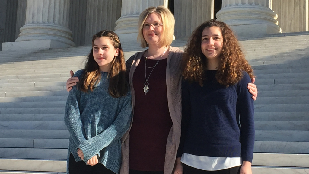 Kendra Espinoza of Kalispell, Mont., stands with her daughters, Naomi and Sarah, outside the U.S. Supreme Court on Wednesday. Espinoza is the lead plaintiff in a case that could make it easier to use public money to pay for religious schooling.