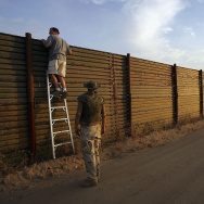 Volunteers look over the US-Mexico border fence to see how illegal border crossers may jump the fence before going on the nightly patrol by citizen volunteers searching for people crossing into the US illegally from Mexico near Campo, California in eastern San Diego County.