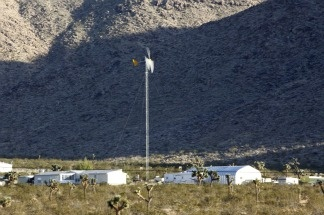 A wind-driven turbine drives an electrical generator on private property near a site proposed for wind turbines in the Mojave Desert near the town of Apple Valley, Calif., on Nov. 8, 2010.