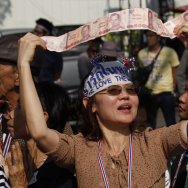 An anti-government supporter displays her donations for the cause during a street rally in Bangkok, Thailand, on Tuesday. Thailand has declared a state of emergency in Bangkok and its surrounding areas to cope with anti-government protests that have stirr