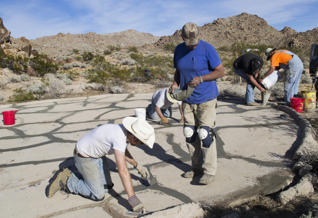 Cliff McDonald (R) helps a Water for Wildlife volunteer patch cracks in a cement drinker.