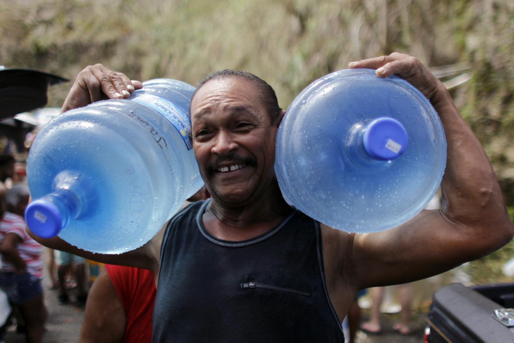 A man carries two water jugs filled with water collected from a natural spring created by landslides in Corozal, west of San Juan, Puerto Rico, on September 24, 2017 following the passage of Hurricane Maria.