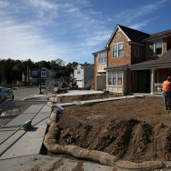 A worker digs a trench in front of a home under construction at a new housing development on March 17, 2015 in Larkspur, California.