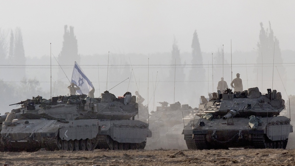 Israeli soldiers stand on their tanks near Israel's border with the Gaza Strip on Tuesday.