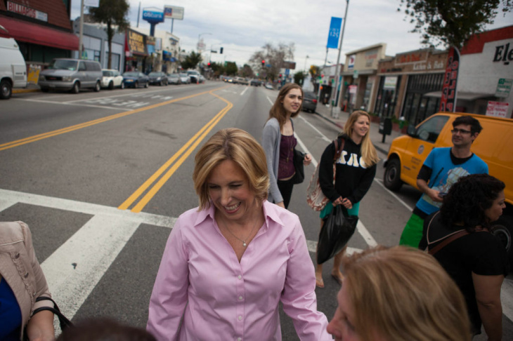 Mayoral Candidate Wendy Greuel comes down the stairs at the opening of her field office in Boyle Heights with her son Thomas, her husband Dean Schramm, Councilman José Huizar and State Assembly Speaker John Pérez.