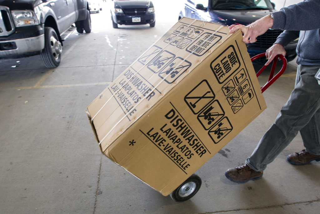 File: In this Wednesday, Feb. 27, 2013, photo, an employees carts a dishwasher to a customer's vehicle at the loading docks of Nebraska Furniture Mart in Omaha, Neb. Orders for durable goods fell 3.4 percent in December following a 2.1 percent decline in November, the Commerce Department reported Tuesday.
