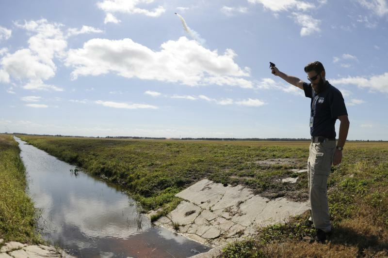 Wildlife biologist Kory McLellan shoots off pyrotechnics to scare birds away from the airfield at MacDill Air Force Base in Tampa. (Photo by Mariette Adams/ U.S. Air Force)