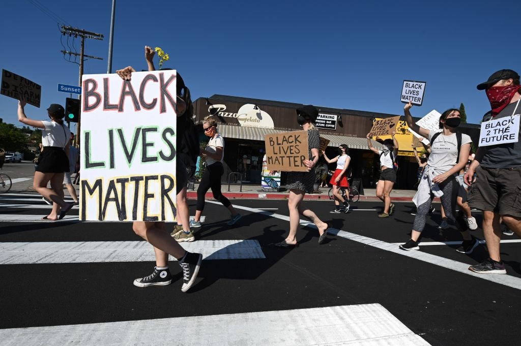 A small group of peaceful protestors hold signs and shout slogans in memory of George Floyd and in opposition to police brutality, in the Silverlake section of Los Angeles, California, June 11, 2020.