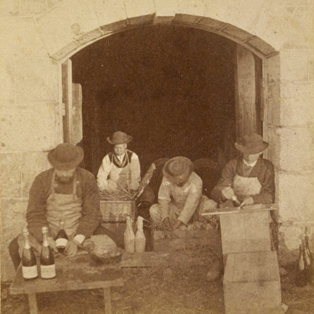 Photos of Chinese men working in the fields and bottling wine are displayed in Buena Vista's tasting room.