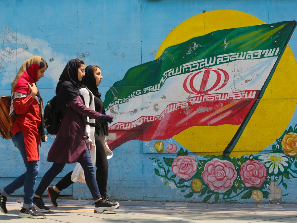 Young women walk past a mural showing the Iranian flag in Tehran on April 23. The White House announced Monday it was ending waivers exempting several countries from U.S. sanctions on Iranian oil exports.