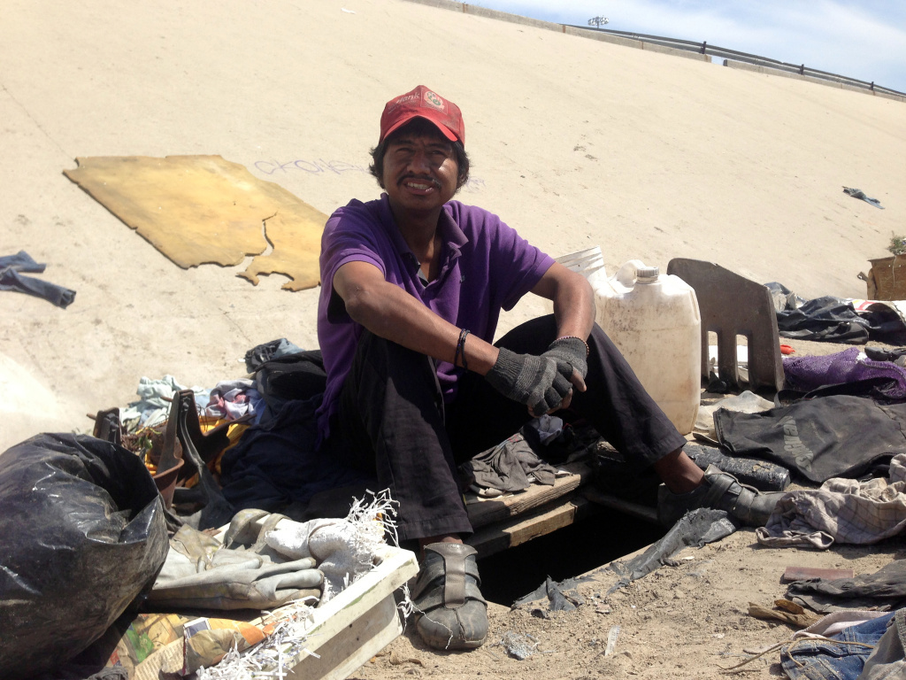 Abimael Martinez, who was deported from Riverside, Calif., with the hole he dug to live in beneath the banks of Tijuana's fetid river canal. Some Mexican deportees wind up homeless in Tijuana, unable to afford the cost of staying in a migrant shelter.
