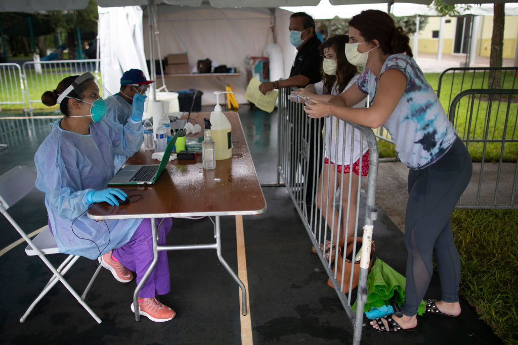 Health care workers take information from Ashley Perez and her daughter Hailey Garcia before they are tested for COVID-19 in a medical tent at a testing site locate at the Miami Lakes Youth Center on July 22, 2020 in Miami Lakes, Florida.