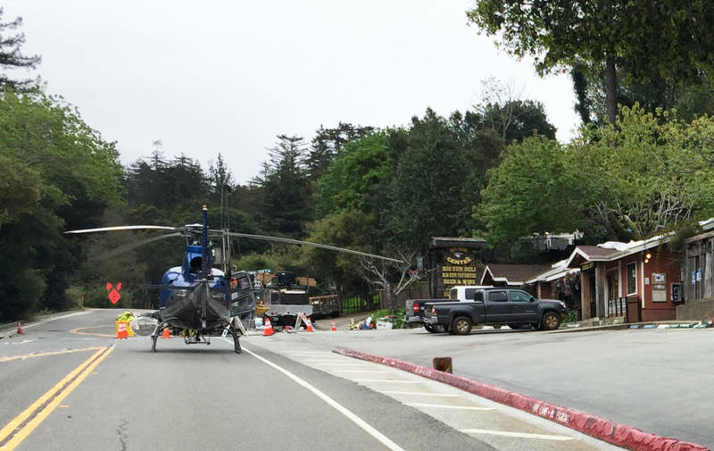 A helicopter sits on Highway 1. Since February, it's been one of the few ways in and out of the area south of the Pfeiffer Canyon Bridge