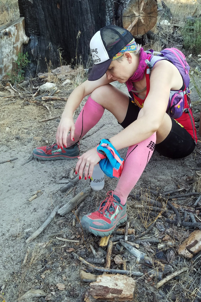 Runner Martine Sesma sits alongside the trail course at about mile 51 of the Angeles Crest 100 trying to gather the strength to continue the run.