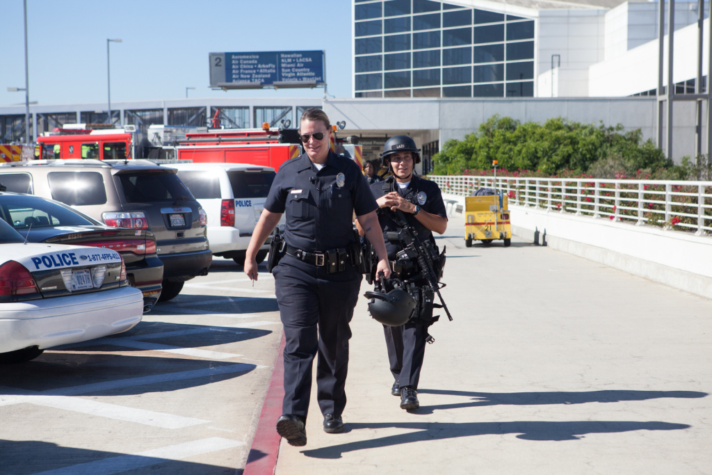 Police officers Leslie Perkins and Fredy Lazlo leave the scene at LAX on November 1st, 2013.