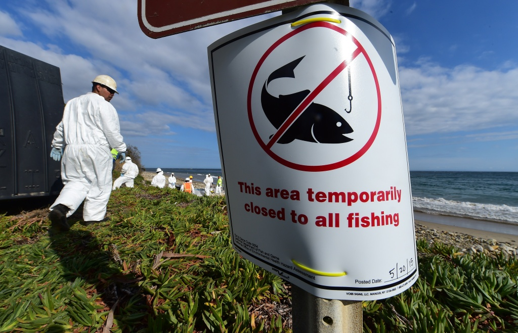 A sign is posted closing the beach to all fishing as an environmental cleanup crew helps with the clearing of oil-tainted items found at Refugio State Beach in Santa Barbara County, in California on May 21, 2015. The governor of California declared an emergency as crews scrambled to contain an oil slick and clean up popular beaches after a pipeline rupture dumped thousands of gallons of oil into the ocean.