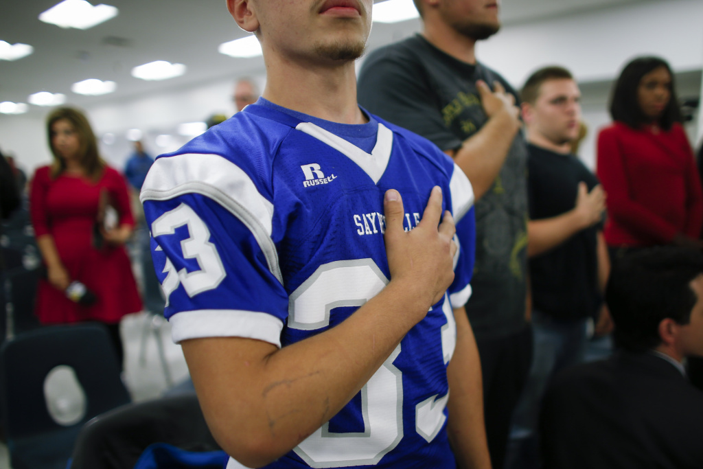 File: A Sayreville football team player stands for the Pledge of Allegiance at a Board of Education meeting to support his team's coaches on Oct. 21, 2014 in Parlin, New Jersey.