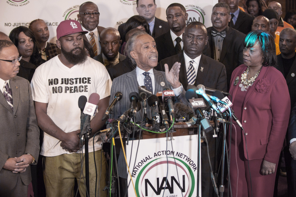 The Rev. Al Sharpton, center, speaks during a press conference at Greater St. Marks Church as Michael Brown Sr. (second from left) and Brown family attorney Benjamin Crump (second from right) look on Nov. 25, 2014, in Dellwood, Missouri. Sharpton addressed the lack of an indictment from a grand jury considering charges against Ferguson police officer Darren Wilson in the shooting death of Michael Brown .