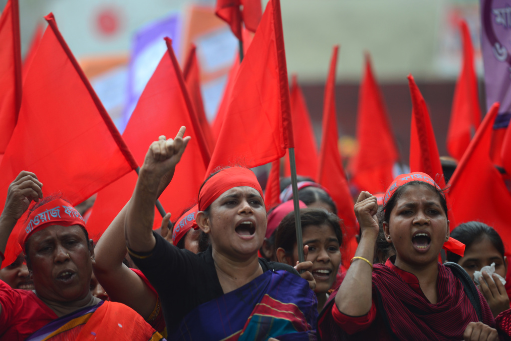 Bangladeshi activists shout slogans and wave flags during a procession to mark May Day, or International Workers Day, in Dhaka on May 1, 2013.