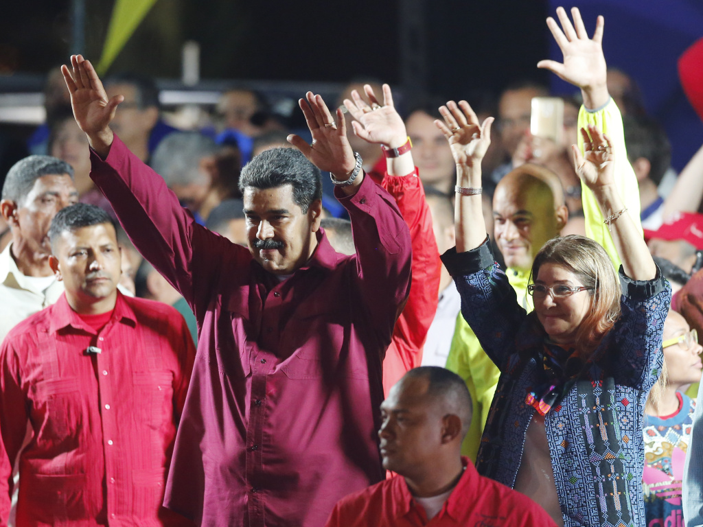 Venezuela's President Nicolas Maduro and his wife Cilia Flores wave to supporters at the presidential palace in Caracas on Sunday after election officials declared his victory.