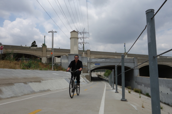 A cyclist bikes alongside the Los Angeles River near the Glendale-Hyperion complex of bridges, which are the subject of reconstruction plans.