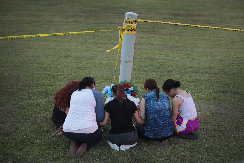 Mourners say a prayer after leaving flowers in front of Santa Fe High School on May 19, 2018 in Santa Fe, Texas. The day before, 17-year-old student Dimitrios Pagourtzis entered the school with a shotgun and a pistol and opened fire, killing 10 people.