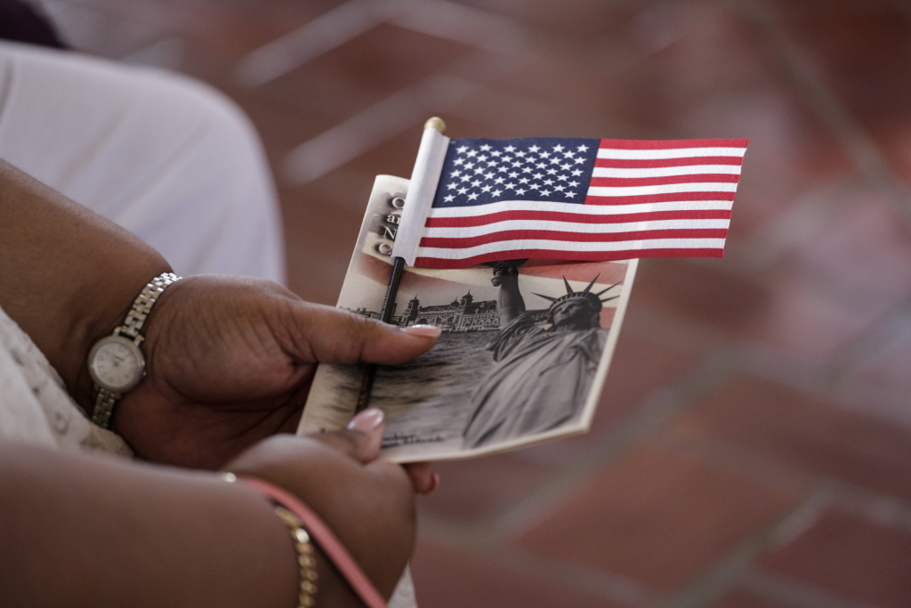 A woman holds a US flag before she became US citizen during a special naturalization ceremony in honor of Citizenship Day and Constitution day Ellis Island in New York on September 16, 2016.