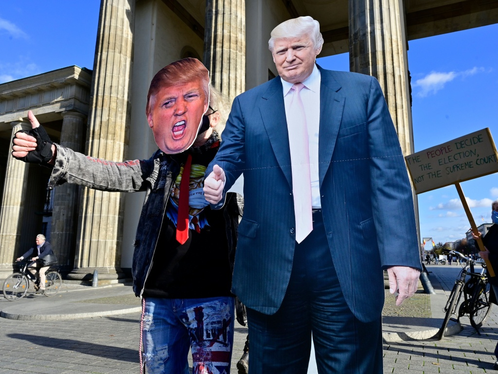 A supporter of President Trump's poses with a cardboard cutout likeness Wednesday in front of the Brandenburg Gate in Berlin.