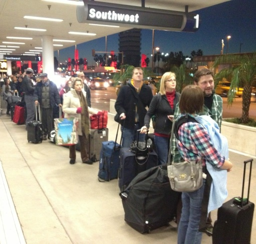 Holiday travelers wait to pass through a secutiry checkpointt outside Terminal 1 at LAX early Friday morning.