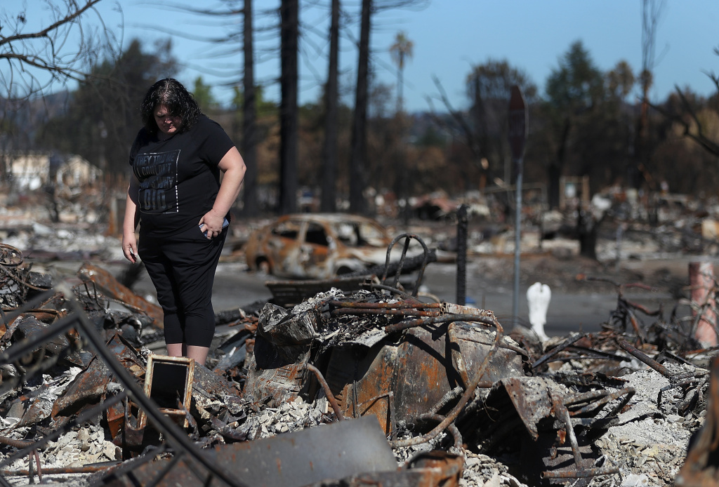 SANTA ROSA, CA - OCTOBER 23:  Renee Hernandez looks over the remains of her Coffey Park home that was destroyed by the Tubbs Fire on October 23, 2017 in Santa Rosa, California. Residents are returning to their homes after a fast moving and deadly widlfire destroyed 8,400 structures and claimed the lives of at least 42 people.  (Photo by Justin Sullivan/Getty Images)