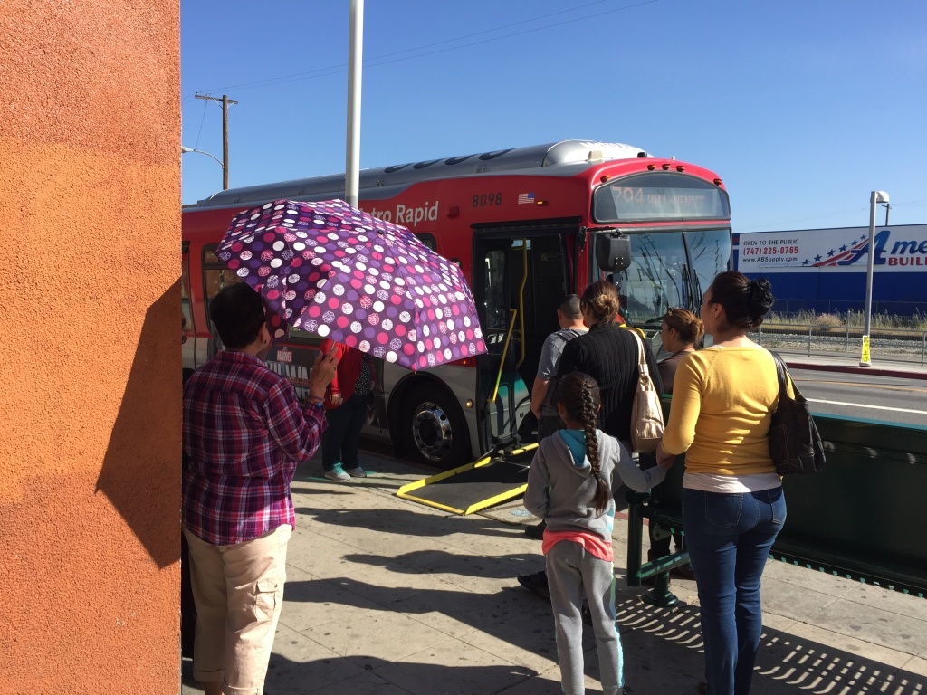 A woman uses an umbrella to stay out of the sun at a bus stop with no shelter on San Fernando Road in Pacoima.