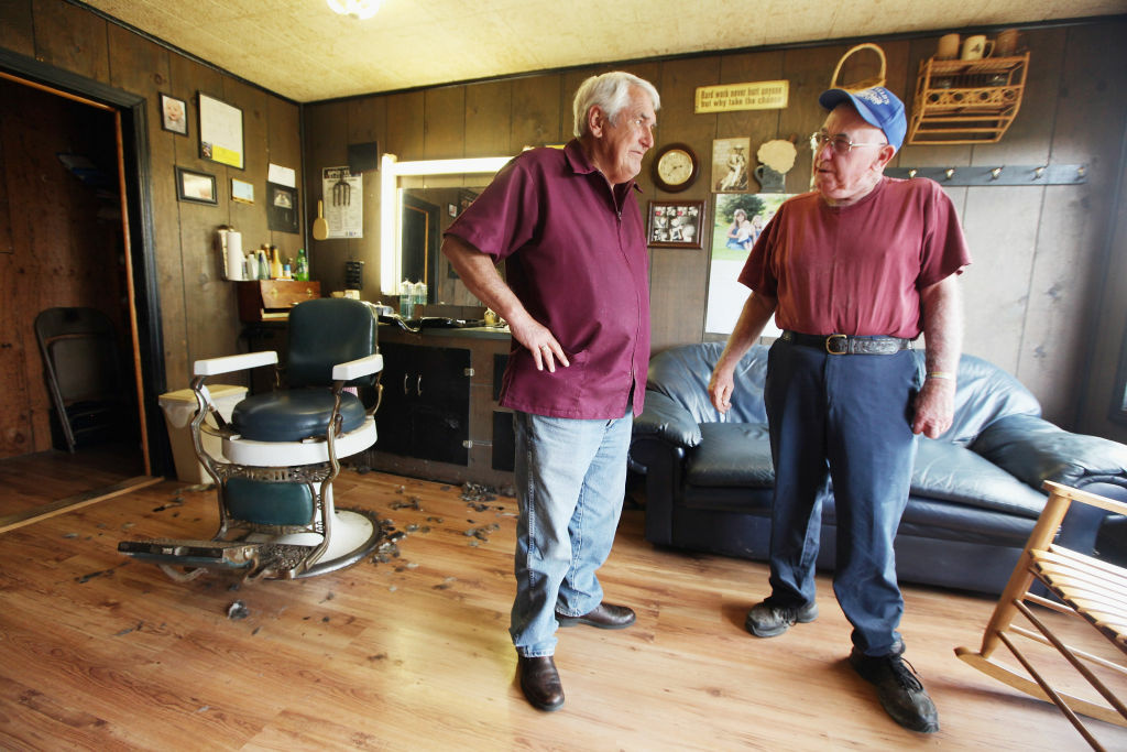 Barber Gary Mays (C) chats with retired butcher Jesse Johnson (R) in Mays' barber shop in Owsley County on April 20, 2012 in Booneville, Kentucky. The 2010 U.S. Census listed Owsley County as having the lowest median household income in the country outside of Puerto Rico, with 41.5% of residents living below the poverty line.