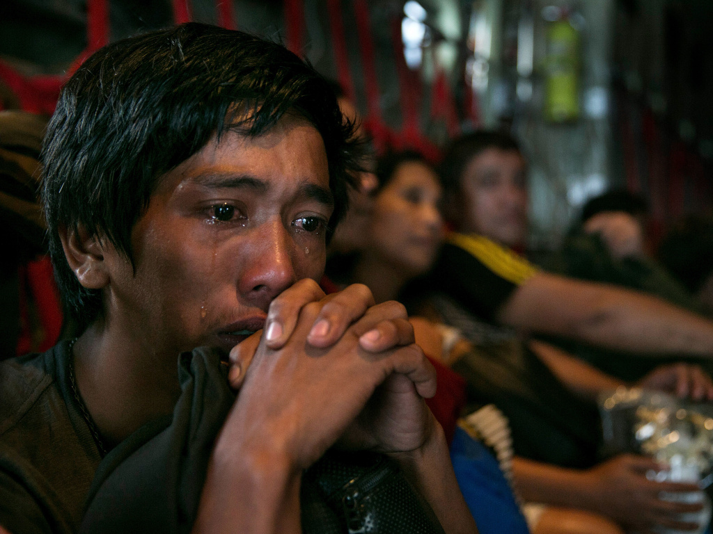 In anguish: Tears ran down the cheeks of a man as he waited with other survivors for a flight out of Tacloban, the Philippines, which was devastated by Typhoon Haiyan.
